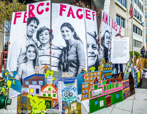 Protesters used huge portraits of harmed families and a miniature town to block the front entrance to FERC's offices.//photo by Eric McGregor