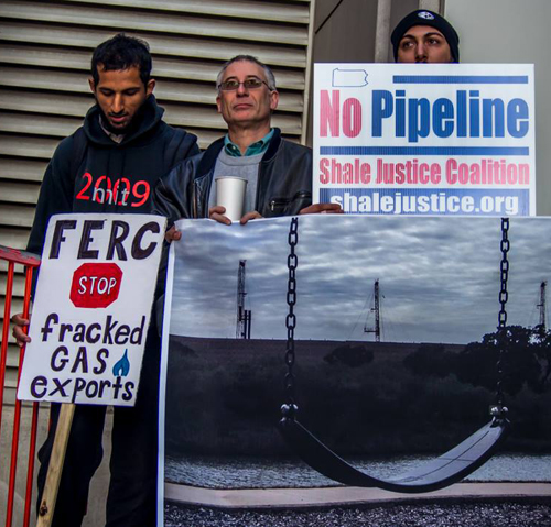 Protesters hold a photo of an empty swing with three frack towers nearby. //photo by Penn Johnson @ Spencerhjohnson.com